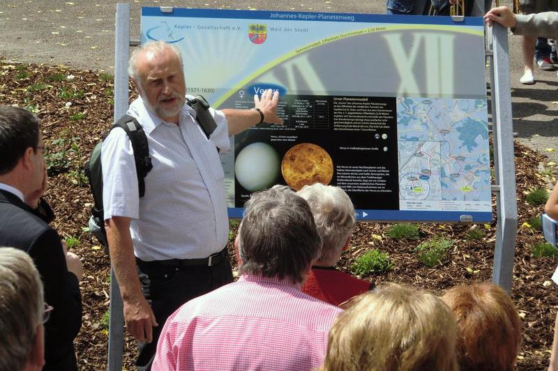 Besuchergruppe vor einer Infotafel des Planetenwegs