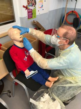 Dr. Hermann demonstriert die Testung an einer Puppe